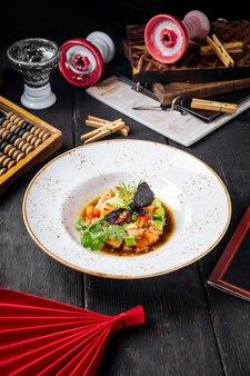 Tartar mit rotem fisch und gemüse in einer sauce
