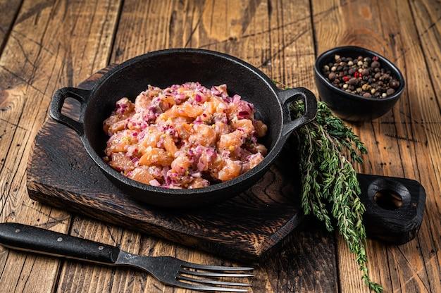 Tartar oder tartar mit lachsfisch, roten zwiebeln, rucola und kapern in einer pfanne. holztisch. draufsicht.