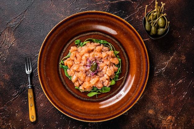 Tartar oder tartar mit lachsfisch, roten zwiebeln, rucola und kapern in rustikalem teller. draufsicht.