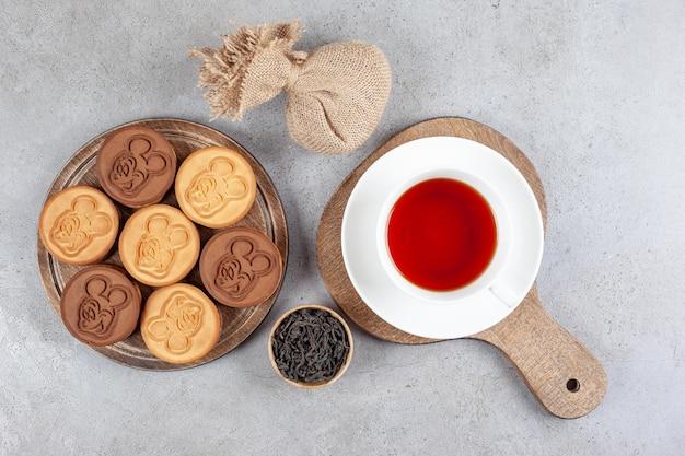 Tarte kekse und eine tasse tee auf holzbrettern neben einer kleinen schüssel teeblätter und einem sack auf marmorhintergrund. hochwertiges foto