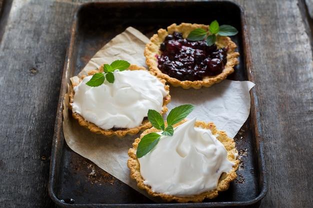 Tarte mit beeren und zuckerguss, sahne, schlagsahne. torte mit sahne öffnen. hochzeit dessert