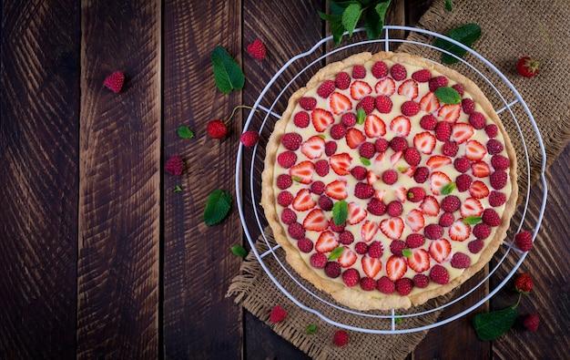 Tarte mit erdbeeren, himbeeren und schlagsahne mit minzblättern dekoriert. draufsicht, überkopf