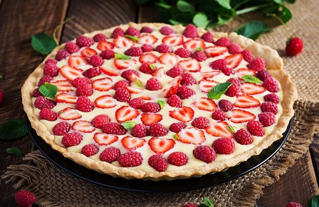 Tarte mit erdbeeren, himbeeren und schlagsahne mit minzblättern dekoriert.