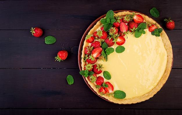 Tarte mit erdbeeren und schlagsahne, angerichtet mit minzblättern. ansicht von oben