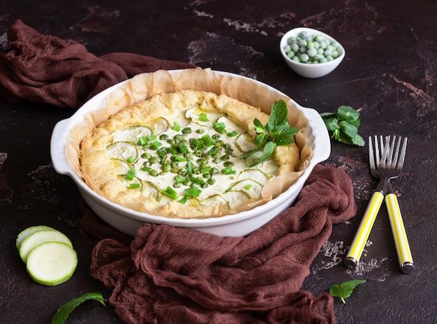 Tarte oder quiche mit zucchini, erbsen, frühlingszwiebeln und ricotta oder sauerrahm.
