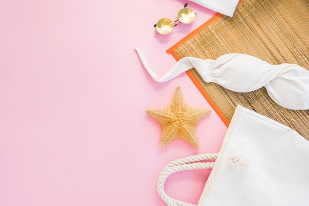Tasche in der nähe von sonnenbrillen und badeanzug unter der matte