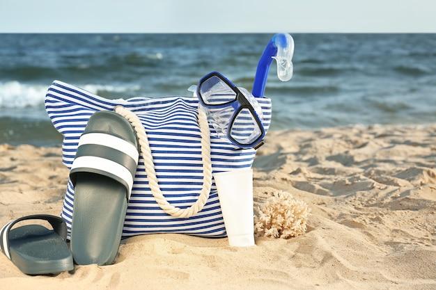 Tasche mit flip-flops, set oder schnorchel und kosmetik am sandstrand
