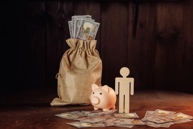 Tasche mit geld, sparschwein und menschenfigur. geschäfts- und investitionskonzept.