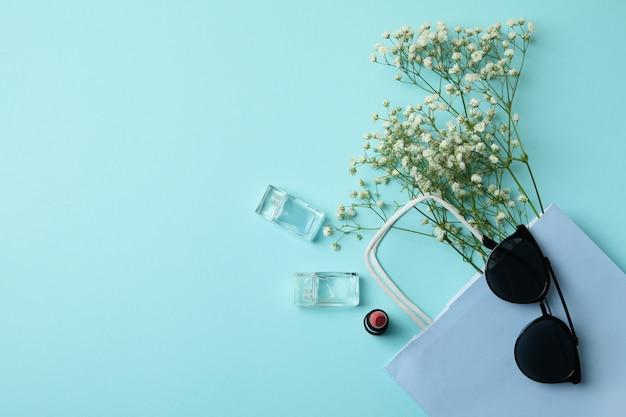 Tasche, sonnenbrille, parfums, lippenstift und blumen auf blauem hintergrund