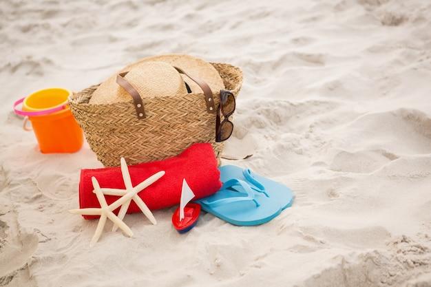 Tasche und strand-accessoires auf sand gehalten
