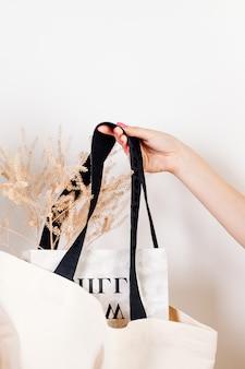 Tasche voller zeitschriften und trockenblumen mocap aus wiederverwendbarer weißer baumwoll-ökotasche auf weißem isoliertem hinterg...