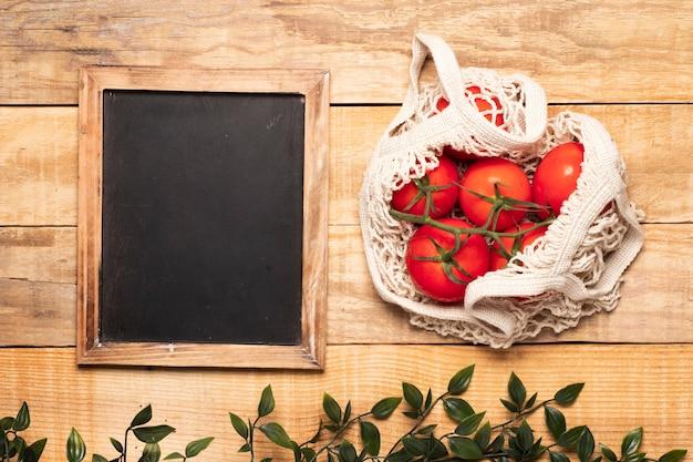 Tasche von tomaten nahe bei leerer tafel