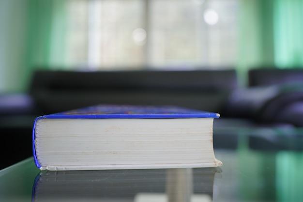 Taschenbuch auf topglass-tisch mit blur-sofa-set im zimmer