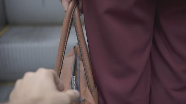 Taschendieb stiehlt smartphone aus orangefarbener handtasche.