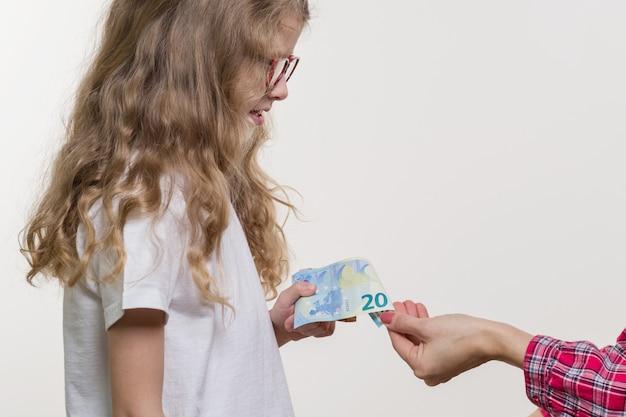 Taschengeld. mama gibt dem kind bargeld.