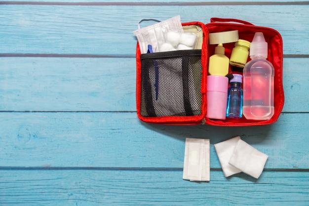 Taschenkind der draufsicht ersten hilfe mit medizinischen bedarfen auf hölzernem hintergrund.