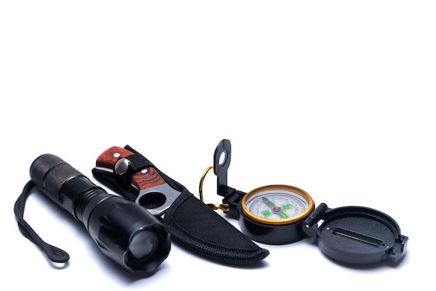 Taschenlampe, messer, kompass auf weißem hintergrund