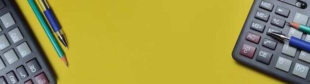 Taschenrechner bleistift und kugelschreiber auf gelbem grund. nahaufnahme. lange fahne.
