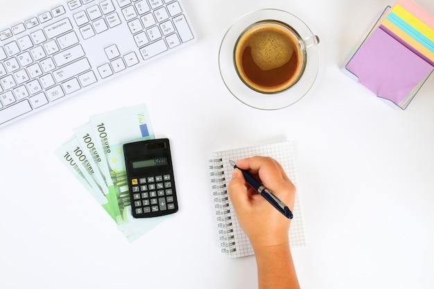 Taschenrechner, eurobanknoten, notizbuch auf einem desktop zu einer kaffeetasse und eine tastatur.
