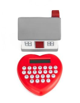 Taschenrechner-herz geformt und miniaturhaus.