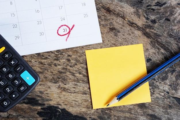 Taschenrechner, kalender, post-it-notiz und bleistift auf dem schreibtisch