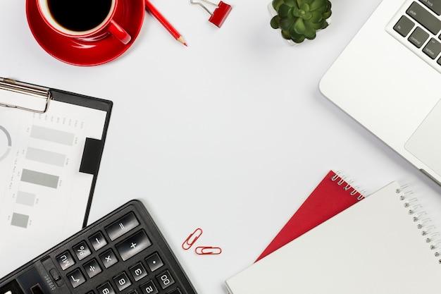 Taschenrechner, laptop, gewundener notizblock, kaffeetasse, kaktuspflanze auf weißem schreibtisch