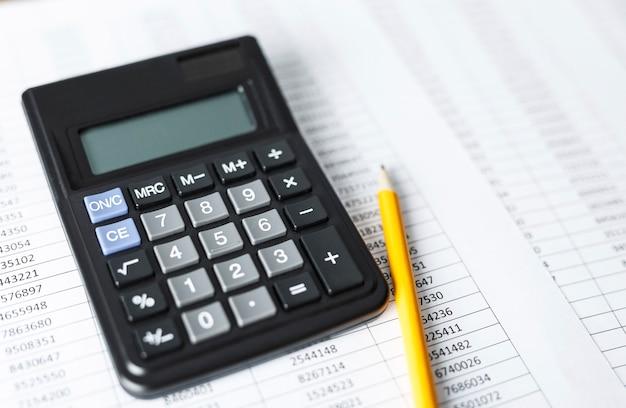 Taschenrechner mit bleistift auf weißem papier mit zahlen