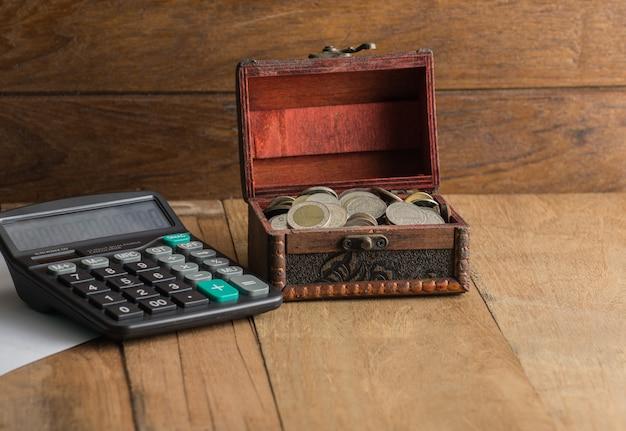 Taschenrechner mit münze in einer kiste auf hölzernem hintergrund