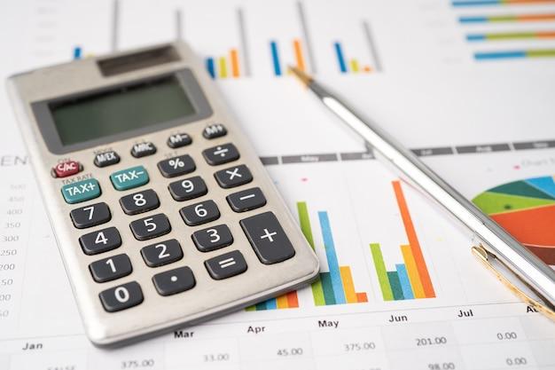 Taschenrechner mit stift auf diagrammpapier mit millimeterpapier finanzkonto-statistik-analyse-wirtschaftskonzept
