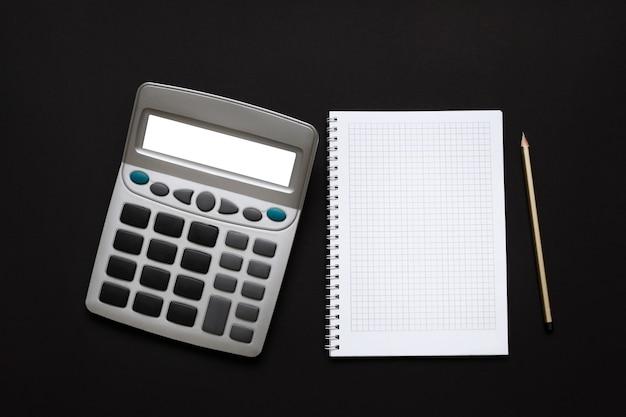 Taschenrechner, notizblock und bleistift auf einer schwarzen oberfläche