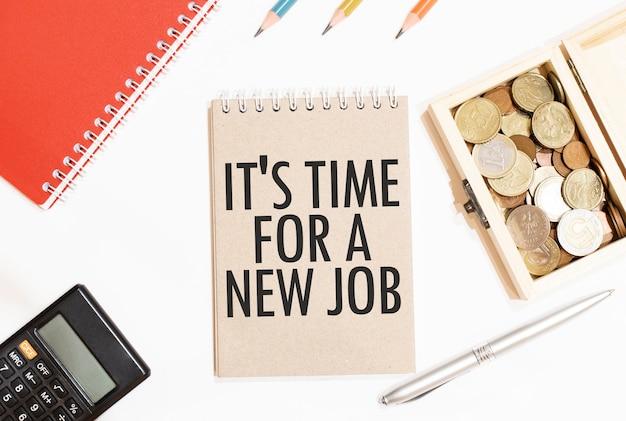 Taschenrechner, roter notizblock, drei farbstifte, silberner stift und braunes notizbuch mit text es ist zeit für einen neuen job