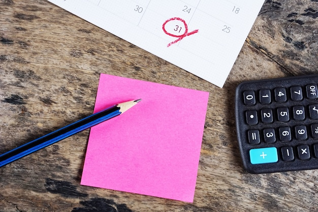 Taschenrechner, stichtagskalender, post-it-notiz und bleistift auf dem schreibtisch
