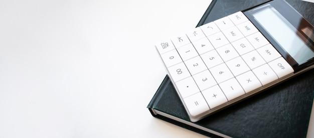 Taschenrechner, stift und leeres notizbuch für das büro auf weißem hintergrund isoliert