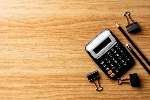 Taschenrechner und büroartikel auf holztisch.