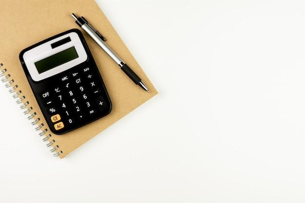 Taschenrechner und büroartikel auf weißer tabelle. - draufsicht mit kopienraum.