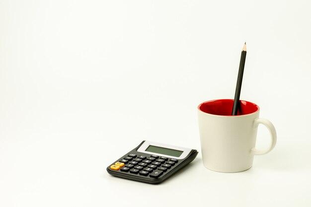 Taschenrechner und ein bleistift in der kaffeetasse auf weißer tabelle.