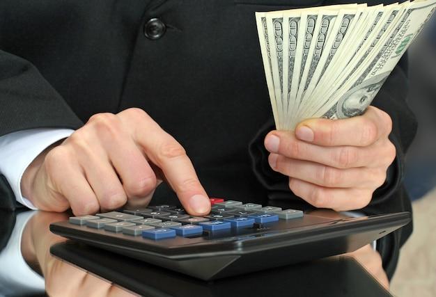 Taschenrechner und geld in der hand von businessnan