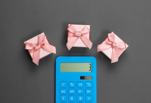 Taschenrechner und geschenkboxen mit schleife auf grau. berechnung des wertes des geschenks.