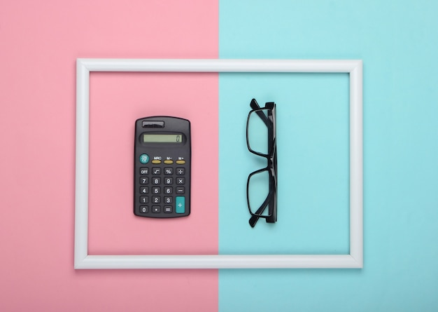 Taschenrechner und gläser im weißen rahmen auf rosa blauer pastelloberfläche