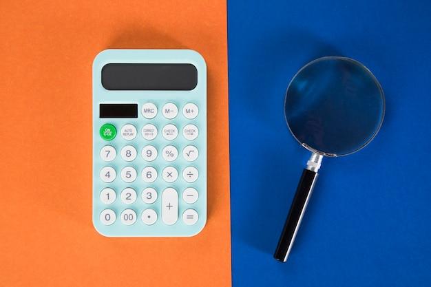 Taschenrechner und lupe auf einem mehrfarbigen tisch