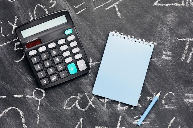 Taschenrechner und notizbuch auf tafel