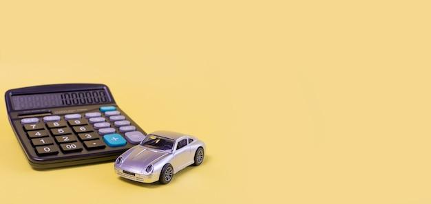 Taschenrechner und spielzeugauto isoliert auf gelbem hintergrund