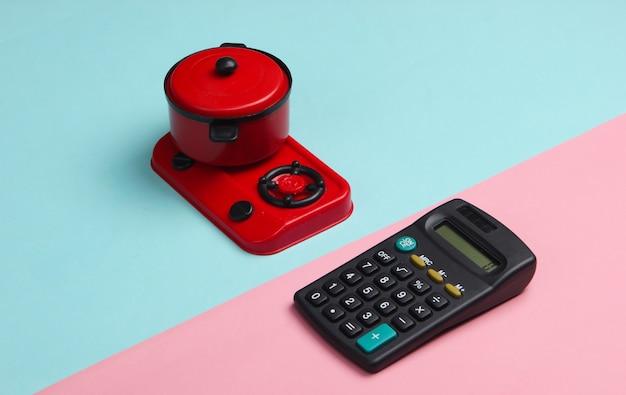 Taschenrechner und spielzeugofen mit pfanne auf einem blau-rosa pastell