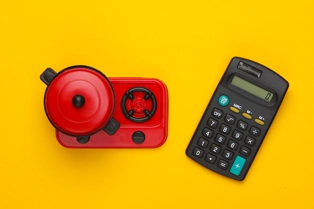 Taschenrechner und spielzeugofen mit pfanne auf gelb