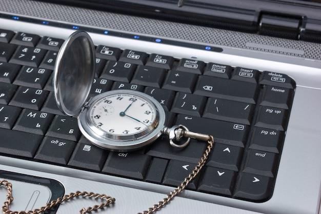 Taschenuhr auf einer laptoptastatur