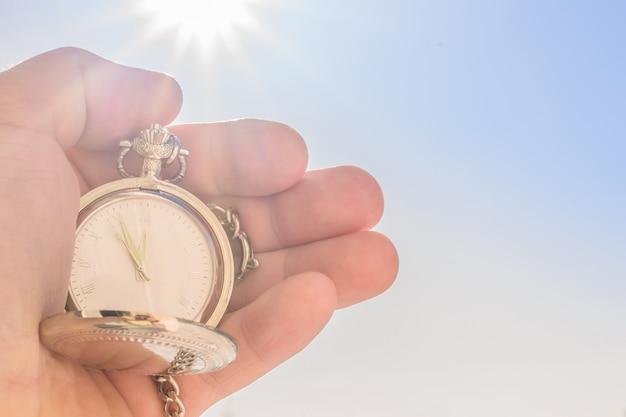 Taschenuhr in der hand und blauer himmel in der sonne.