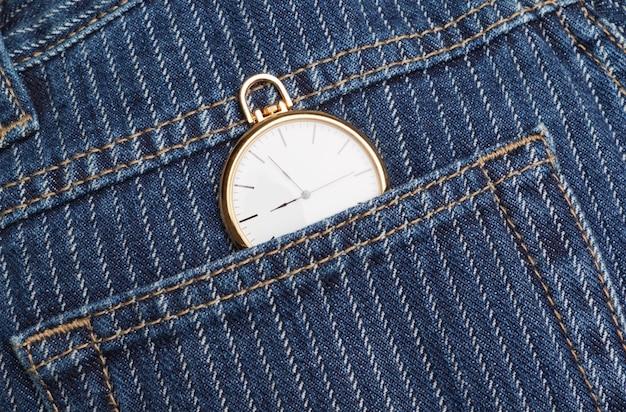 Taschenuhr in einer jeanshose. nahansicht.