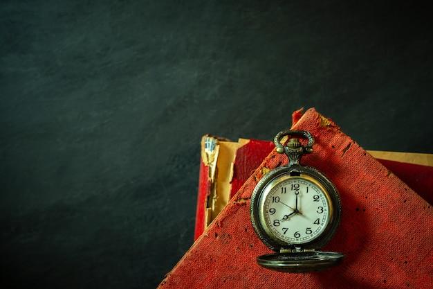 Taschenuhr und altes buch auf zementboden.