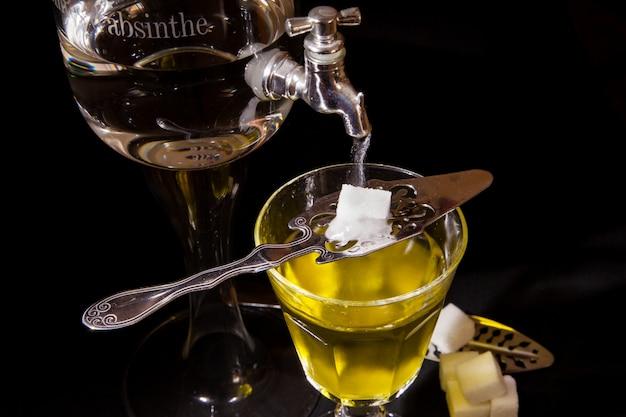 Tasse absinth mit einem springbrunnen und einem löffel mit zucker