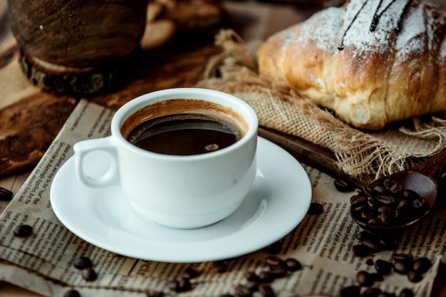 Tasse americano kaffee auf zeitung gelegt